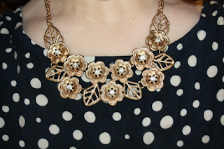 outfit post featuring a crochet waist polka dot navy dress with gold floral collar necklace on a girl with ombre hair