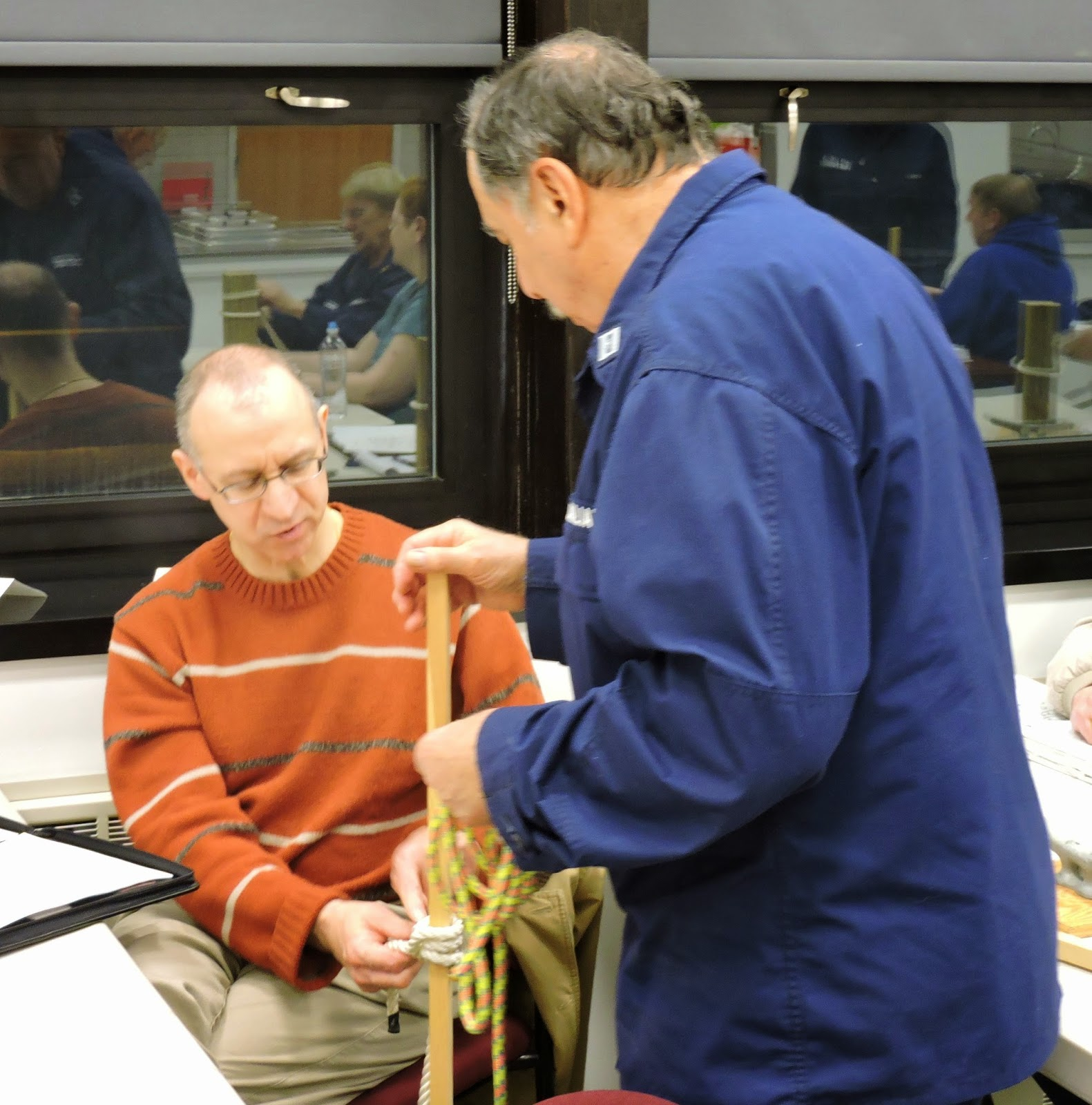 Phil Licetti,sitting,Flotilla 16-08 ties a clove hitch for Bill Costagno,Instructor from Flotilla 16-07