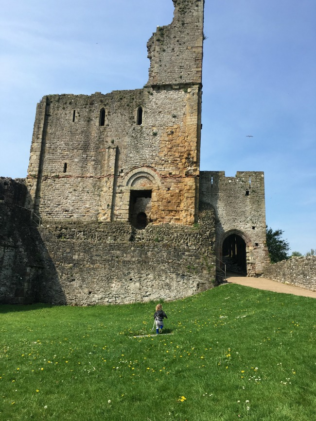 ruins and toddler running on grass