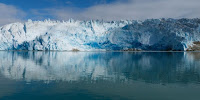 A coastal glacier in southern Greenland mirrored in the sea. (Image Credit: Claire Rowland / Flickr) Click to Enlarge.