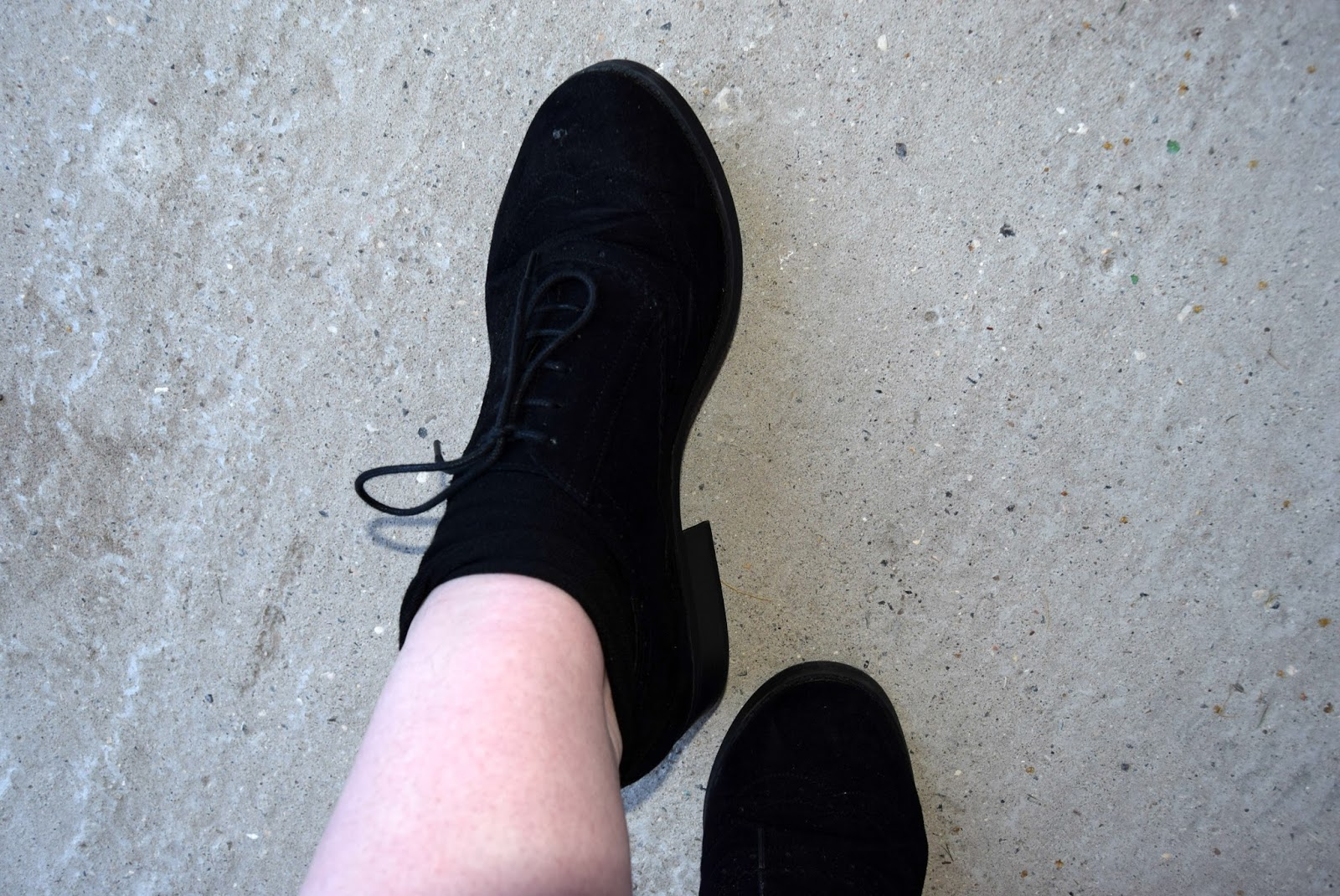 A photo of some black school shoes paired together with some black socks