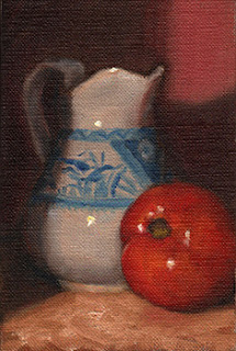 Oil painting of a blue and white porcelain jug beside a red tomato.