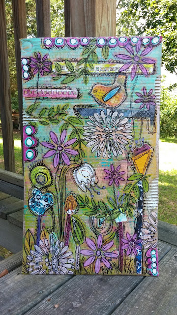 a colorful mixed media piece on cardboard with whimsical birds and flowers
