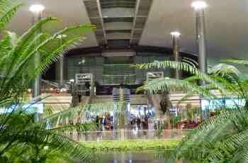 Reisende ruhen sich auf dem Flughafen Dubai  - erschöpft zwischen Palmen liegend -  vom Shoppen aus