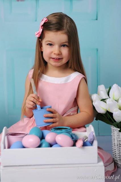 Wielkanocny portret czteroleniej dziewczynki malujacej pisanki