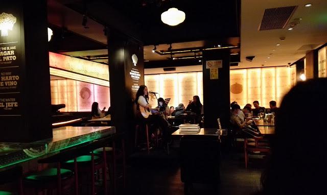 バーの内部…女性シンガーがギターを弾きながら歌っている
