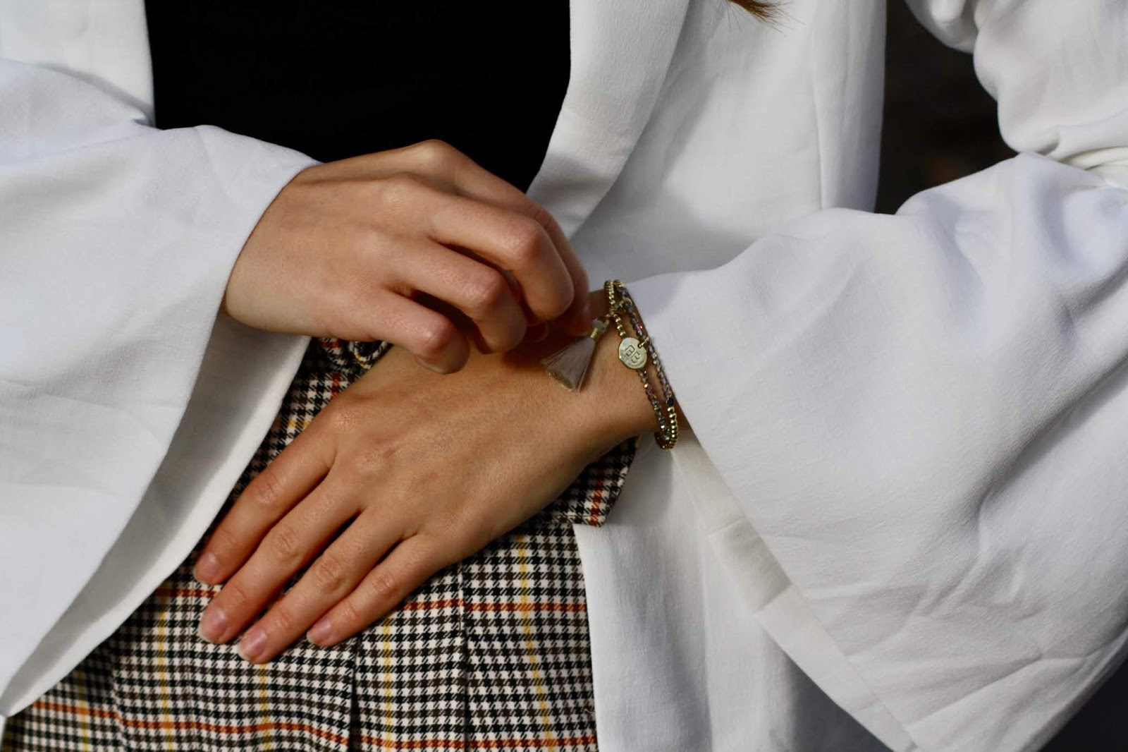 close up of abbey's hands and bell shape sleeves, with a gold tasselled bracelet
