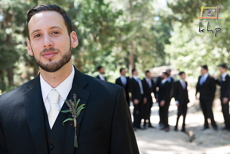 The groom poses for the camera while his groomsmen are hanging out at the beautiful Pine Rose Cabins