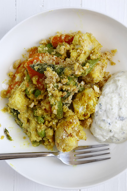 A plate with a curried savoury crumble and cucumber raita