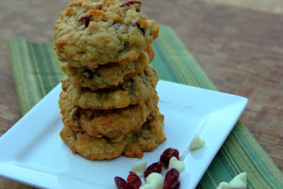stack of oatmeal cranberry white chocolate chip cookies on a white plate with green napkin