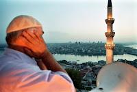 İstanbul'da cami şerefesinde akşam ezanı okuyan bir müezzin