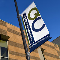 Photo of building with communiversity at queen creek banner/flag