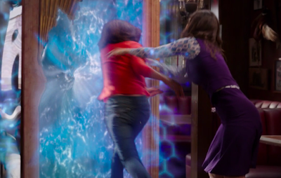 Janet shoves a demon through the portal, which is a large wooden door with a watery blue electric field in the middle.