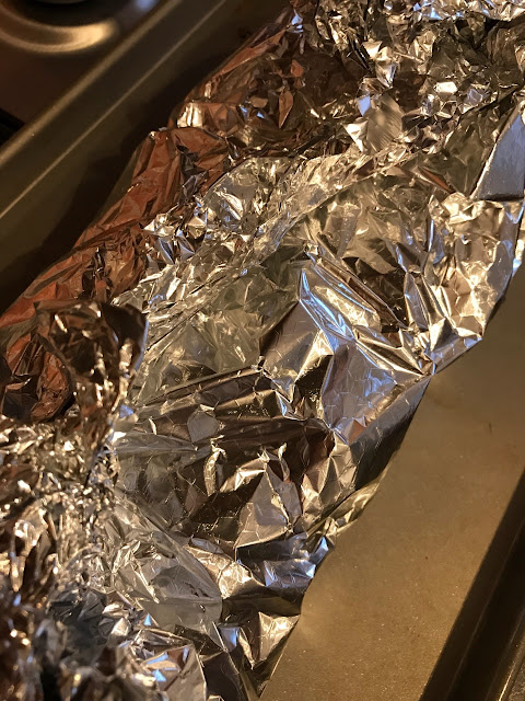 Bread wrapped in foil and on a baking tray