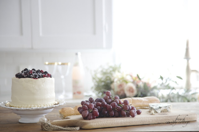 berry topped cake with grapes in kitchen