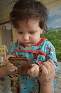 Ребёнок держит в руках сотовый телефон