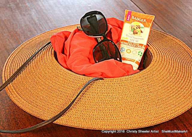 Wide brimmed hat, protective sun shirt, sunglasses, tangerine & vanilla sunscreen