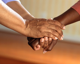 One person uses both hands to clasp the right hand of another person.