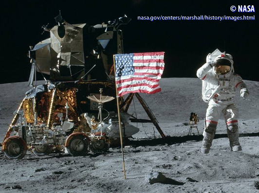 Apollo 16 mission commander John W. Young salutes the USA flag next to the lunar module and moon-roving vehicle.