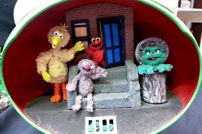 Miniature Sesame Street stoop with Big Bird, Elmo, Grover and Oscar on it.