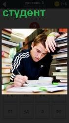 студент за столом вокруг которого находятся книги для учения