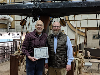 Two men stand in front of a replica of a ship's mast and rigging. Man on left wears a dark long-sleeved shirt and is holding a framed certificate. Man on right has a beard and wears a long-sleeved shirt and quilted vest. Both are wearing glasses.