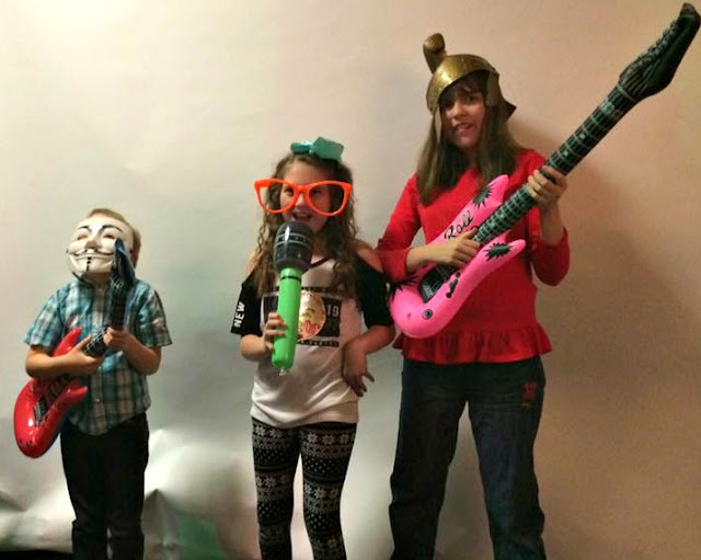 3 children using inflatable guitars and microphone, masks and hats in a party photo booth.