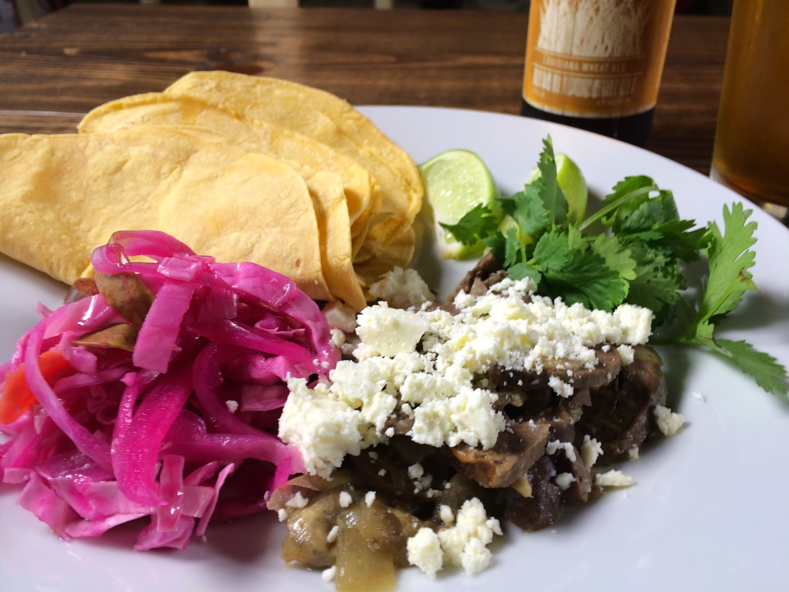 Braised Heart Taco: Slow Cooked Lamb Heart, Cilantro, Curtido, Lime, and Feta. Pictured with a Parish Brewing Co. Canebrake.