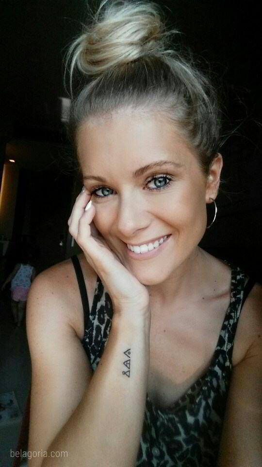 Preciosa mujer rubia con tatuajes de triángulos de glifos
