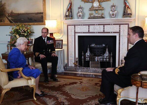 Queen Elizabeth received the outgoing and incoming Commanding Officers of HMS Queen Elizabeth. blue dress and diamond brooch