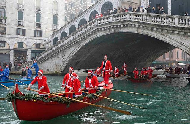 Pessoas com roupas de Natal andando de gôndola em canal de Veneza