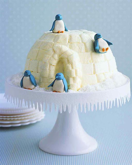 "Piped buttercream-frosting blocks mengubah kue es krim cokelat vanilla menjadi igloo yang disebut penguin marzipan manis di rumah. Serpihan-serpihan kelapa kering ""salju"" dan dadu kue yang dipangkas dengan es batu yang dilapis gula melengkapi habitat es"