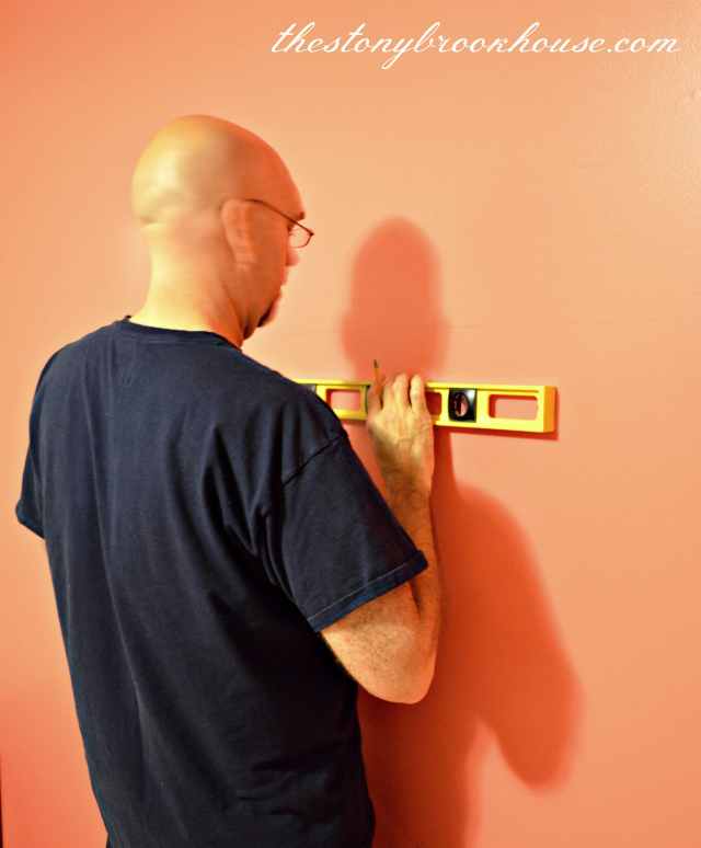 Dad measuring to attach headboard to wall
