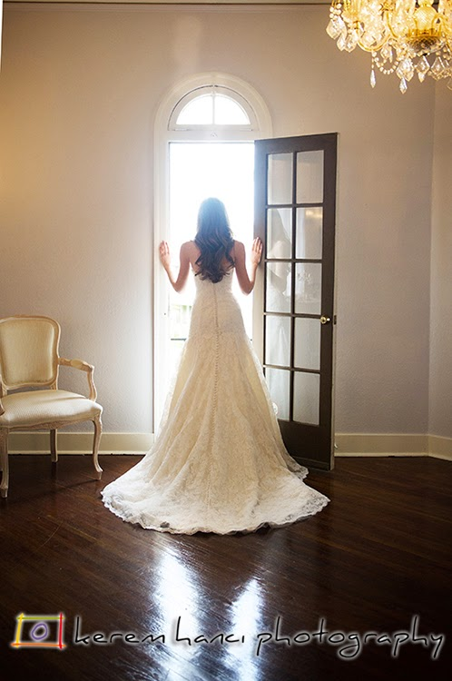 A classic wedding photograph with the bride by the french door.