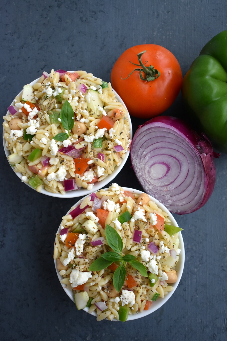 Greek Orzo Pasta Salad is an easy filling salad loaded with tomatoes, feta cheese, cucumbers, orzo pasta, garbanzo beans, a Greek vinaigrette and more! Perfect for entertaining and meal prep. www.nutritionistreviews.com