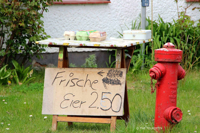 A red water hydrant next to a table selling 10 eggs for EUR 2.50 which has to be paid cash into a money box sitting on the table also..