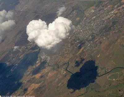 Lustige Wolke in Herzform schwebt über die Erde