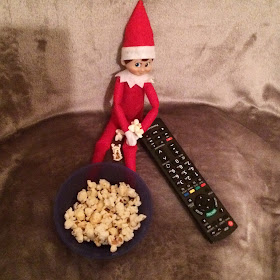Elf on the shelf having popcorn and watching a movie