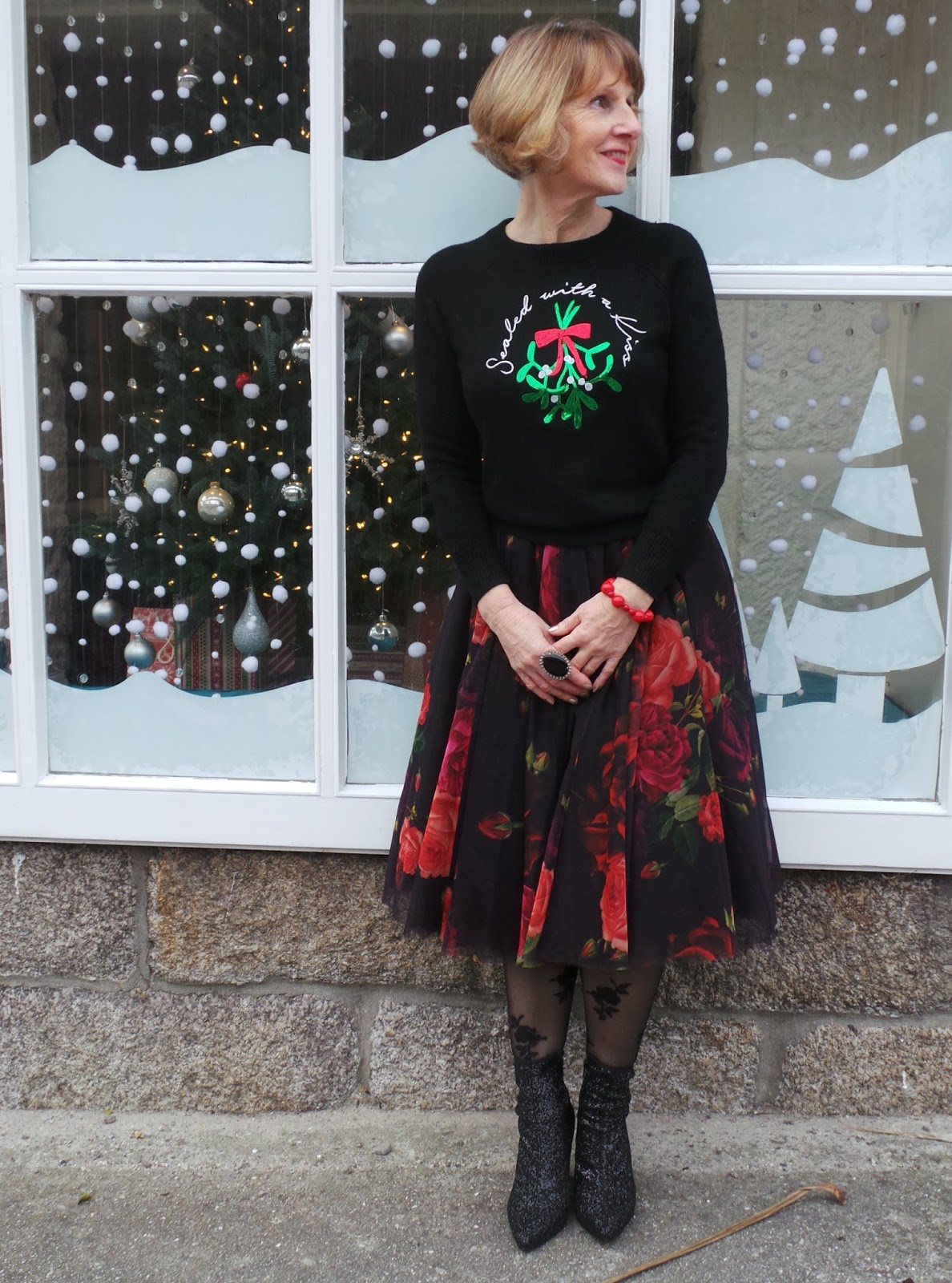 Image showing Quirky over 50s fashion blogger Anna Parkes from Annas Island Style posing outside a festive shop wearing a Christmas jumper with floral midi skirt and sparkly boots