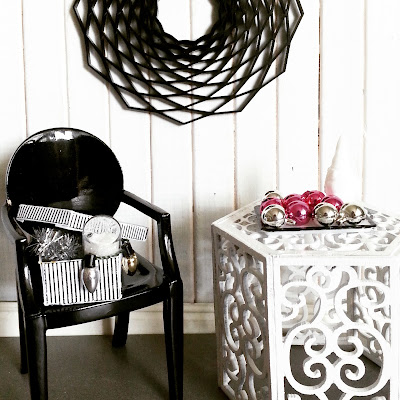 Modern miniature scene of a black ghost chair next to a white scrollwork side table. On the chair is a shoebox filled with Christmas decorations, and on the table, a tray displaying Christmas baubles in  silver and hot pink.