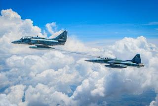 Descrição: Foto em dia de céu azul com nuvens: dois aviões caça em voo com proa à esquerda, a uma certa distância e em níveis diferentes. À frente e em nível mais alto, o A-4 Skyhawk da Marinha Brasileira, aeronave de ataque, bombardeiro e multifunção, com motor turbojato, com capacidade de abastecimento a mais de 22 000 pés com transferência de até 2.200 litros de combustível por minuto. O sistema de reabastecimento do caça A-4 da Marinha do Brasil estende a mangueira em direção ao F-5M da Força Aérea Brasileira,um caça leve, com motores turbojato, bimotor monoplano, projetado na aplicação de aviônicos de última geração, nos sistemas de navegação, armamentos e auto-defesa. O contato é feito em pleno ar, no final da mangueira, situa-se o drogue, acoplador com forma afunilada, que é estabilizado por uma cesta. A aeronave recebedora possui um probe (na parte externa, preso a fuselagem, à direita próximo ao cockpit envidraçado) que acopla o drogue e permite a transferência de combustível em voo.