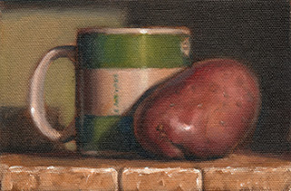 Oil painting of a Désirée potato beside a green and white coffee mug.
