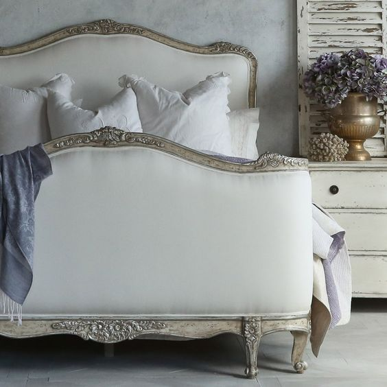 Beautiful French farmhouse style bedroom with ornate bed, weathered shutter,and white furniture