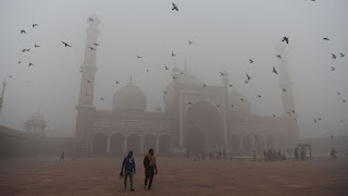 Indian visitors walk through the courtyard of Jama Masjid mosque amid heavy smog in New Delhi. (Credit: Sajjad Hussain / AFP/Getty Images) Click to Enlarge.