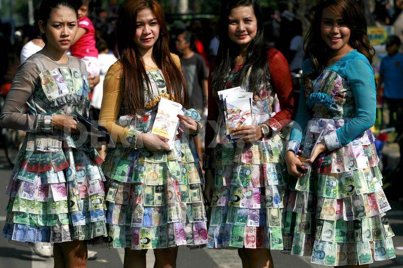 Promosikan money changer, gadis cantik ini pakai baju dari uang kertas