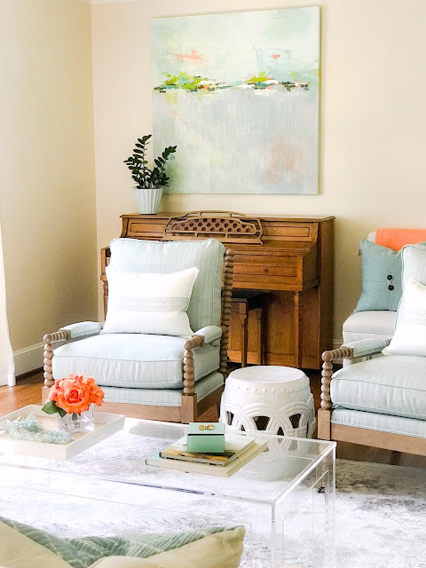 Light blue upholstery and a modern acrylic coffee table with a tray layered with decor - design by Sherry Hart. Come discover more inspiring trays for layering and vignettes in Adding Tray Très Chic to Your Home.
