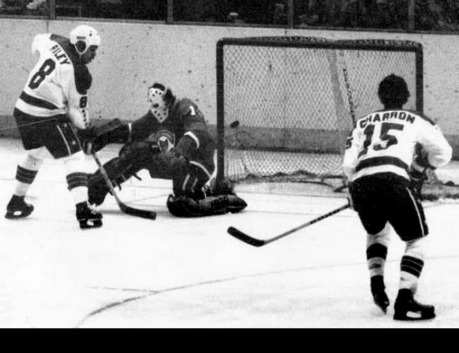 Vs. Cleveland: Bill Riley scores as Guy Charron looks on