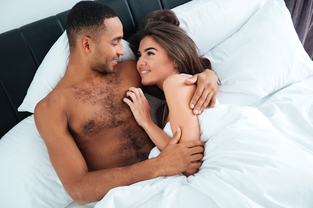 Happy young couple lying and hugging in bed