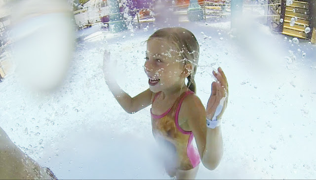 Little girl splashes in the water at Adventure Landing's Shipwreck Island