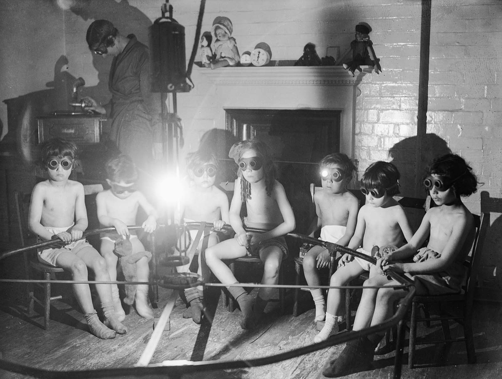 Stripped to the waist and wearing goggles, children sit round a lamp having sun ray treatment while they listen to the gramophone at the East End Mission in Commercial Rd, London. 1931.
